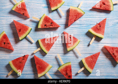Slices of juicy red watermelon on a wooden background - Stock Photo
