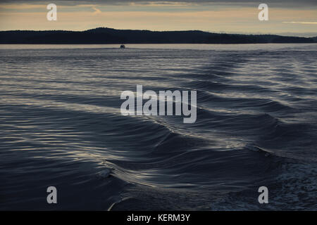 Early morning sailing, a distant boat has created a wake that reflects the silver sky on a progressive pattern of - Stock Photo