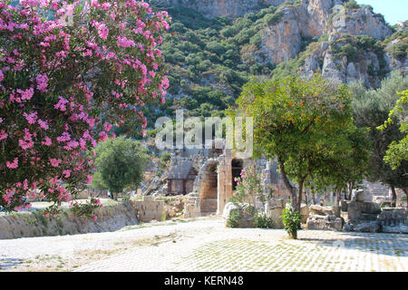 Picturesque views of the ruins of the ancient theater on the background of mountains, flowering trees with purple - Stock Photo