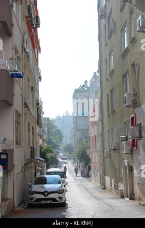 Turkish empty residential narrow street with typical concrete buildings. Road with parked cars. Morning. Vertical - Stock Photo