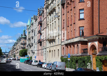 view of the street with a classic Swedish homes, Scandinavian style of red brick and yellow plaster, the cars are - Stock Photo