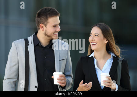 Happy couple of executives walking towards camera and conversing on the street with an office building in the background Stock Photo