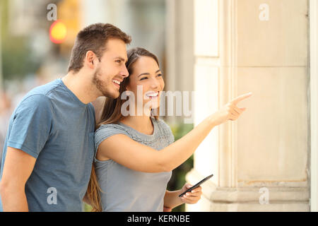 Couple of shoppers watching a storefront and pointing products on the street - Stock Photo
