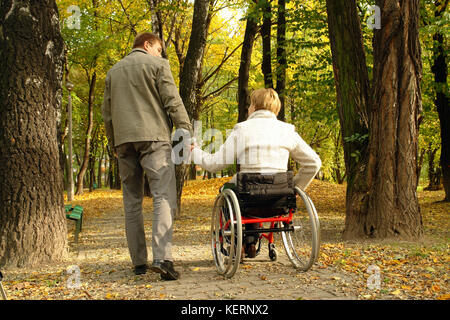 Husband and handicapped wife taking stroll in park alley in fall time - Stock Photo