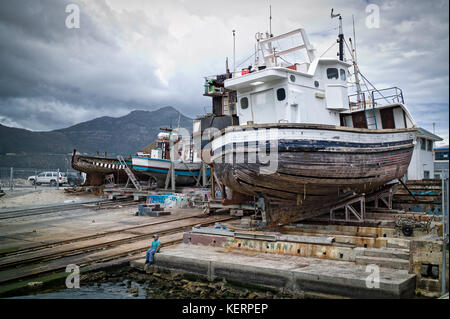 A young boy sits in shipyard with ships being repaired in Hout Bay Harbor, Cape Town, South Africa. - Stock Photo