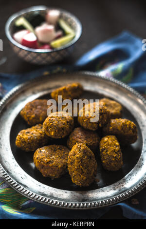 Falafel on a vintage tin plate and a salad of fresh vegetables side view - Stock Photo