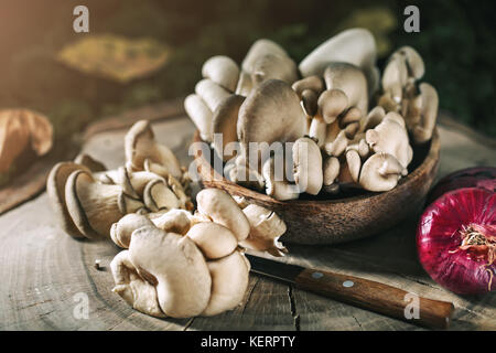 Raw mushrooms on the stump and autumn leaves. Autumn still-life. Selective focus. Autumn background. - Stock Photo