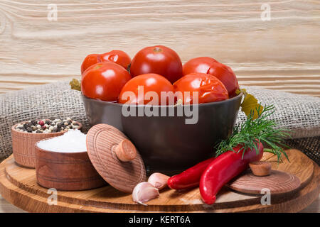 canned tomato in a plate with spices on a wooden background - Stock Photo