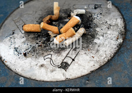 outdoor street ashtray with cigarette filter tips - Stock Photo
