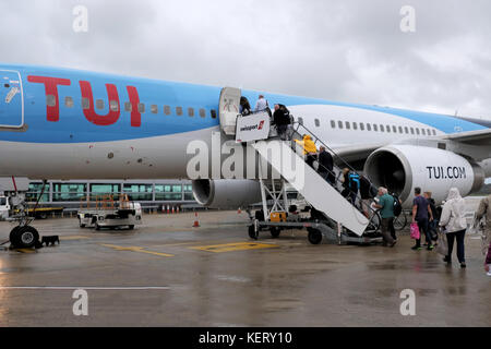 A TUI aircraft standing on the airport apron at Bristol airport in the rain. The aircraft is being boarded by passengers - Stock Photo