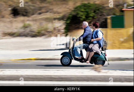 An elderly couple, man and woman, speeding along the road on an old scooter on the island of Rhodes. Neither are - Stock Photo