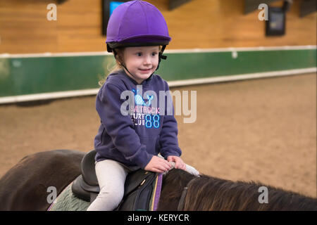 Young Child Horse Riding Lesson Instruction Wearing Purple Hat Helmet - Stock Photo