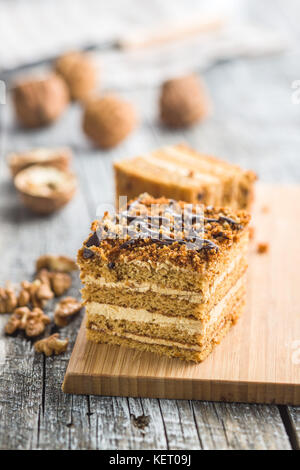 Cake with walnuts and honey on old wooden table. - Stock Photo