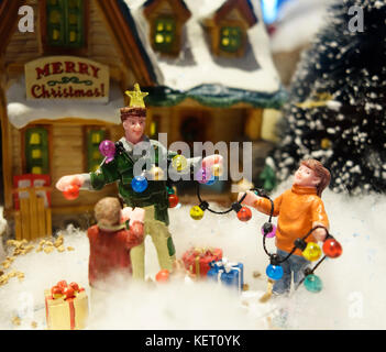 A family playing in the snow at christmas - Stock Photo