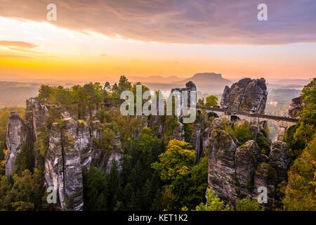 View of Bastei bridge, Bastei at sunrise, in the back the Lilienstein, Elbe Sandstone Mountains, Rathen - Stock Photo