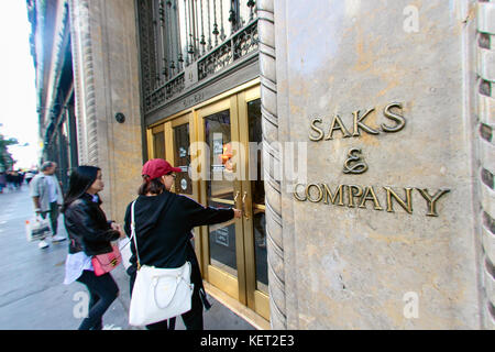 People are walking into the flagship Saks Fifth Avenue department store on Fifth Avenue in New York City. - Stock Photo