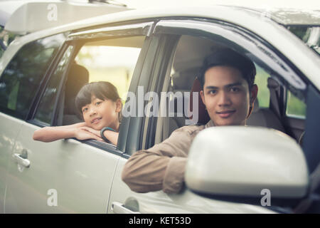 happy little girl  with asian family sitting in the car for enjoying road trip and summer vacation - Stock Photo