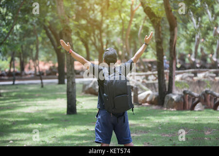 Freedom traveler man standing with raised arms and enjoying a beautiful nature and cheering young woman backpacker - Stock Photo