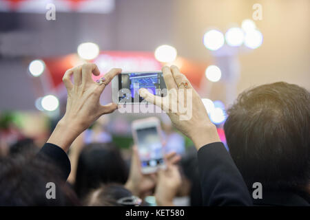 Asian old women holding smartphone and tapping screen for taking pictures. - Stock Photo