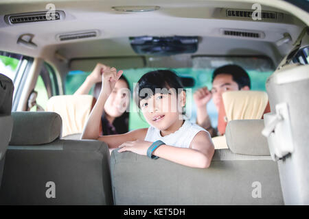 Happy little girl  with asian family sitting in the car for enjoying road trip and summer vacation in camper van - Stock Photo