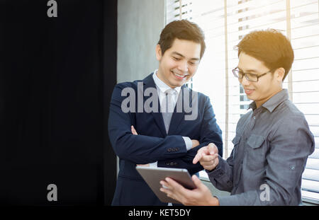 Two Asian handsome businessmen using touchpad with partners discussing documents and ideas at meeting and  smiling - Stock Photo