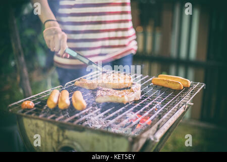 Asian group of Friends making barbecue and grilled shashliks on grate party in outdoor garden - Stock Photo
