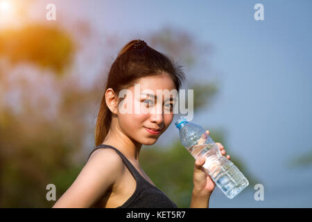 Sporty woman asia drinking water outdoor on sunny day - Stock Photo