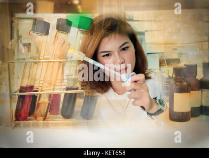 Double exposure Young female tech or women science working and holding pipette in biological laboratory - Stock Photo