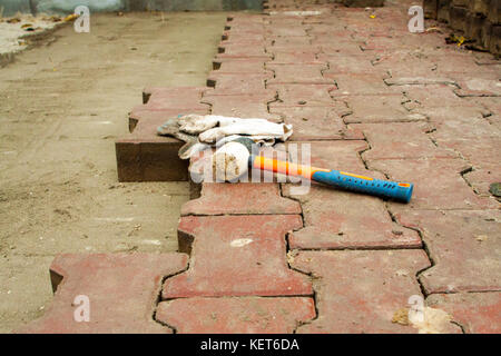 Laying Paving Slabs by mosaic close-up. Road Paving, construction. Workers laying stone paving slab. Laying colored - Stock Photo