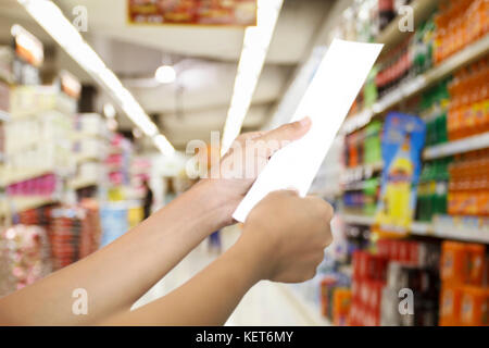 hand of woman asia checking a bill and a long receipt of supermarket/mall for background and shopping fashion and - Stock Photo