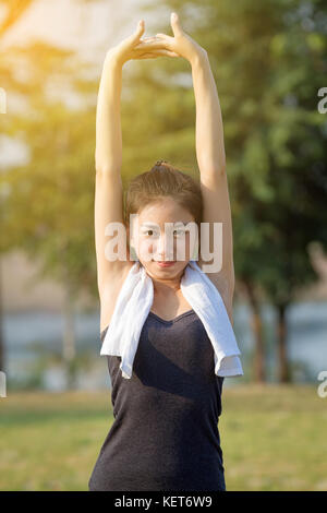 Athletic woman asian warming up and Young female athlete sitting on an exercising and stretching in a park before - Stock Photo
