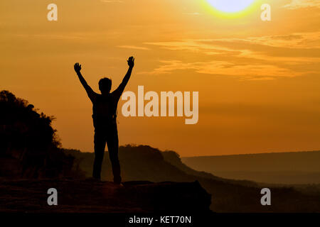 silhouette of man show arm up for achievements successful and celebrating success with sunrise - Stock Photo