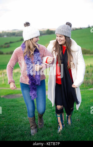 two young girls / sisters walking through fields in  autumn - Stock Photo