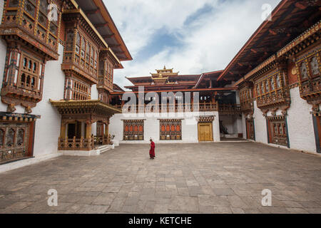A buddhist monk dressed in red walks in the sacred monastery Thimphu Wangdue Bhutan Asia - Stock Photo