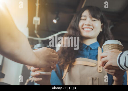 Asian barista giving coffee to customer in her shop. Selective focus. Cafe restaurant service, food and drink industry - Stock Photo