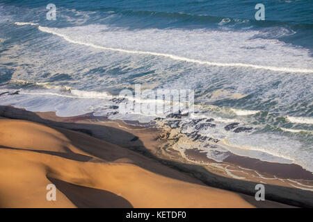 Aerial view of waves of the Atlantic Ocean crashing against the sandy dunes of the Namib desert Namibia Southern - Stock Photo