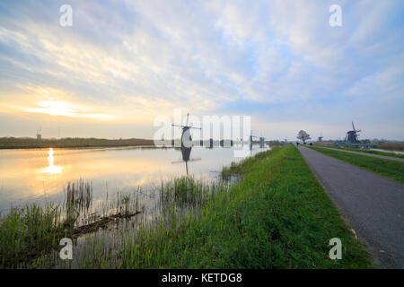 Dawn on windmills reflected in the canal surrounded by green meadows Kinderdijk Molenwaard South Holland The Netherlands - Stock Photo