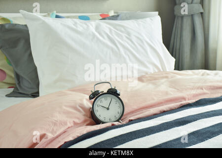 black alarm clock on bed with colorful bedding - Stock Photo