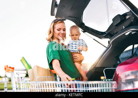 Mother with baby boy putting shopping into back of car. - Stock Photo