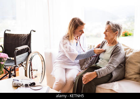 Health visitor and a senior woman during home visit. - Stock Photo