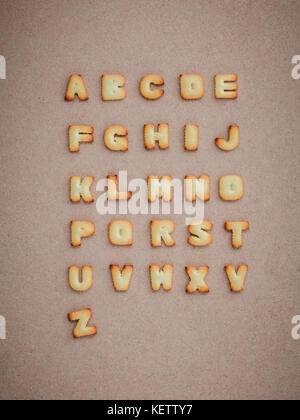 Cookies ABC in the form of alphabet A-Z on brown cardboard background, Valentines day - Stock Photo