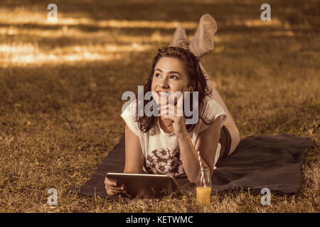 Smiling young teenage girl using digital tablet while lying in green spring garden - Stock Photo