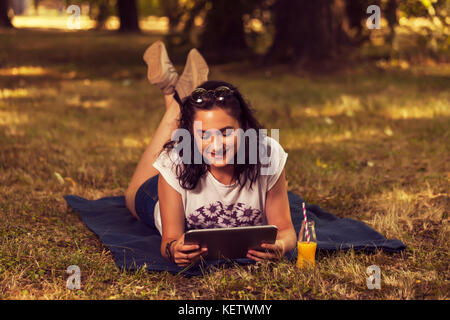 Young beautiful teenage girl lying on a blanket in nature and using a digital tablet, outdoors - Stock Photo