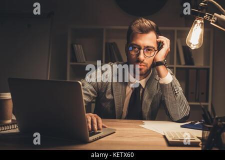 businessman in dark empty office - Stock Photo