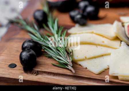 Slices of cheese, olives and rosemary on board - Stock Photo