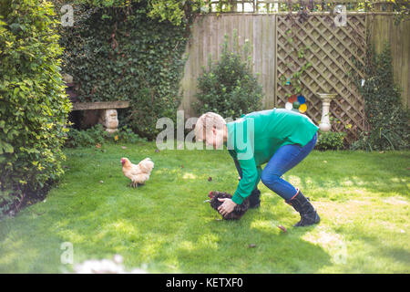 Lady chasing her bantam chicken pets - Stock Photo