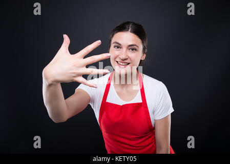 Pretty supermarket female with apron counting five fingers and smiling - Stock Photo