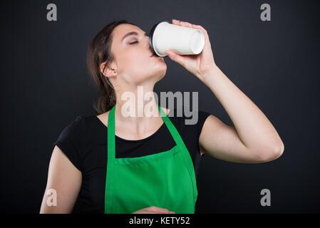 Beautiful brunette seller tasting a fresh espresso in her time break isolated on dark background - Stock Photo