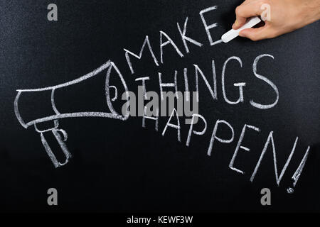 Close-up Of Make Things Happen Text Written On Blackboard - Stock Photo