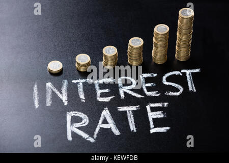 High Angle View Of Stacked Coin With Interest Rate Concept Written On Blackboard - Stock Photo